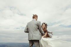 Jeunes mariés magnifiques tenant des mains et dansant au ciel et au Cl Images stock