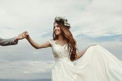 Jeunes mariés magnifiques tenant des mains et dansant au ciel et au Cl Photo stock