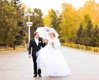 Jeunes mariés marchant en parc d'automne Images stock