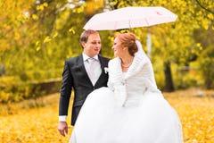 Jeunes mariés marchant en parc d'automne Photos libres de droits