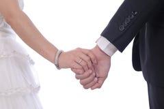 Jeunes mariés marchant ensemble tenant leurs mains Photo stock