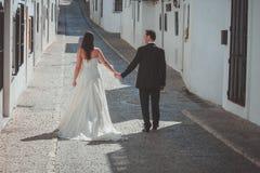Jeunes mariés marchant le long de la rue photographie stock