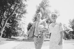 Jeunes mariés marchant loin en parc d'été dehors Photographie stock libre de droits