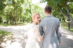 Jeunes mariés marchant loin en parc d'été dehors Image stock