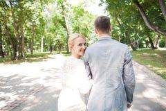 Jeunes mariés marchant loin en parc d'été dehors Images stock