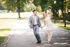 Jeunes mariés marchant loin en parc d'été dehors Photo stock