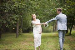 Jeunes mariés marchant loin en parc d'été dehors Photographie stock
