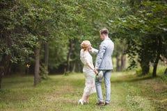 Jeunes mariés marchant loin en parc d'été dehors Image libre de droits