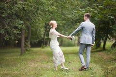 Jeunes mariés marchant loin en parc d'été dehors Photos libres de droits