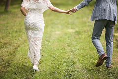 Jeunes mariés marchant loin en parc d'été dehors Photos stock
