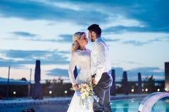 Jeunes mariés marchant près de la piscine image stock