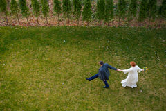 Jeunes mariés marchant sur l'herbe verte Image libre de droits