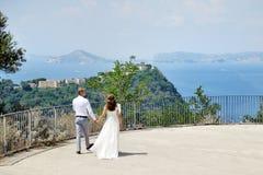 Jeunes mariés marchant tenant des mains à Naples, Italie Images stock