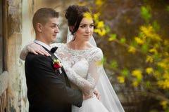 Jeunes mariés posant et étreignant près du vieux closeu de mur de bâtiment Photo stock