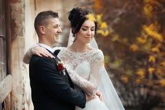Jeunes mariés posant et étreignant près du vieux closeu de mur de bâtiment Images libres de droits