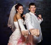 Jeunes mariés posant pour l'appareil-photo avec des boucles sur des mains Photo stock