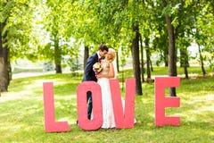 Jeunes mariés près de la lettre l'amour de mot, amour de mot composé de lettres Photos libres de droits