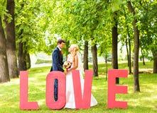 Jeunes mariés près de la lettre l'amour de mot, amour de mot composé de lettres Photo stock
