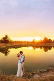 Jeunes mariés près du lac au temps de coucher du soleil Photos libres de droits