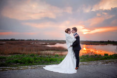 Jeunes mariés près du lac le soir au coucher du soleil Photographie stock libre de droits