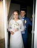 Jeunes mariés regardant hors de la fenêtre de chambre d'hôtel Photo libre de droits