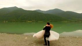 Jeunes mariés romantiques de date près de la rivière sur le fond des montagnes pittoresques clips vidéos