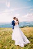 Jeunes mariés romantiques de nouveaux mariés posant sur le champ d'herbe ensoleillé Forest Hills éloigné avec le ciel merveilleux Photographie stock libre de droits