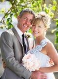 Jeunes mariés romantiques Embracing Outdoors photographie stock libre de droits