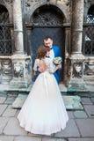 Jeunes mariés romantiques sensuels de nouveaux mariés étreignant devant vieux bulding avec des colonnes Image stock