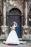 Jeunes mariés romantiques sensuels de nouveaux mariés étreignant devant vieux bulding avec des colonnes Photos libres de droits