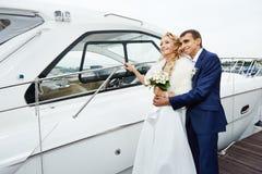 Jeunes mariés romantiques sur le pilier avec le yacht Image stock