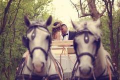 Jeunes mariés s'asseyant dans un chariot blanc Image libre de droits