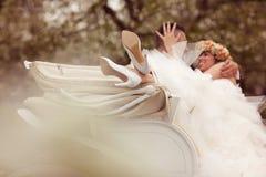 Jeunes mariés s'asseyant dans un chariot blanc Images libres de droits