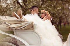 Jeunes mariés s'asseyant dans un chariot blanc Images stock