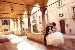 Jeunes mariés s'asseyant près du vieux bâtiment Photos stock