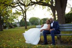 Jeunes mariés s'asseyant sur un banc de parc au coucher du soleil dans un paysage coloré image stock