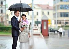 Jeunes mariés se cachant de la pluie Image stock
