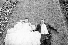 Jeunes mariés se trouvant sur la pelouse avec la guerre biologique de fleurs Photographie stock libre de droits