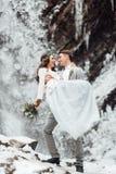 Jeunes mariés sur la cascade de montagne Photo stock