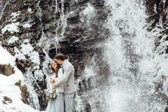 Jeunes mariés sur la cascade de montagne Images stock