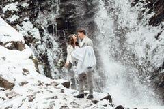 Jeunes mariés sur la cascade de montagne Image libre de droits