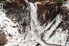 Jeunes mariés sur la cascade de montagne Photographie stock
