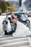 Jeunes mariés sur la rue près de la voiture Photographie stock libre de droits