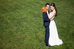 Jeunes mariés sur le fond d'herbe verte Photos stock