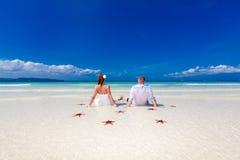 Jeunes mariés sur le rivage tropical de plage avec des starfis rouges Photo libre de droits