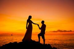 Jeunes mariés sur une plage tropicale avec le coucher du soleil dans le backg Photos stock