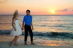 Jeunes mariés sur une plage tropicale avec le coucher du soleil dans le backg Images stock