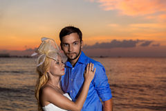 Jeunes mariés sur une plage tropicale avec le coucher du soleil dans le backg Photos libres de droits