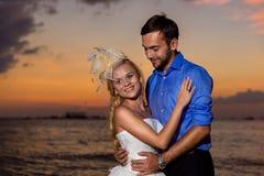 Jeunes mariés sur une plage tropicale avec le coucher du soleil dans le backg Images libres de droits