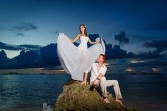 Jeunes mariés sur une plage tropicale avec le coucher du soleil dans le backg Photographie stock